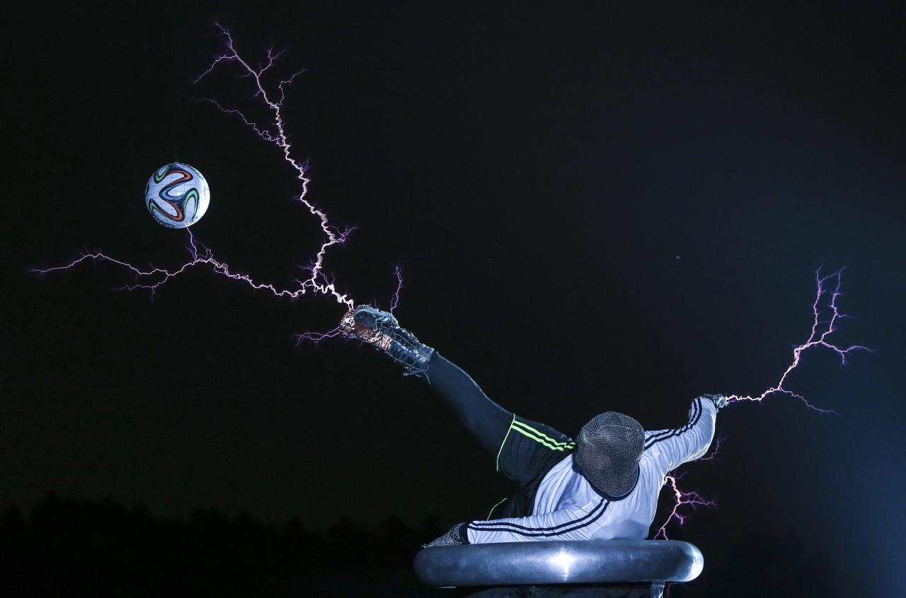 A member of the Thunderbolt Craziness band wearing a metal suit kicks a soccer ball as electricity is discharged from Tesla coils during a performance to celebrate the 2014 Brazil World Cup, in Changle, Fujian province June 12, 2014. The band specialises in producing electric arcs from Tesla coils that have been charged with one million volts of electricity. Picture taken June 12, 2014. REUTERS/Stringer (CHINA - Tags: SPORT SOCCER WORLD CUP SOCIETY TPX IMAGES OF THE DAY) CHINA OUT. NO COMMERCIAL OR EDITORIAL SALES IN CHINA