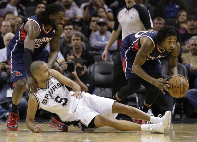Atlanta Hawks' Cartier Martin, right, steals the ball as San Antonio Spurs' Tony Parker (9), of France, fall to the floor during the second half of an NBA basketball game, Monday, Dec. 2, 2013, in San Antonio. Atlanta Hawks' DeMarre Carroll, left, assists on the play. (AP Photo/Eric Gay)