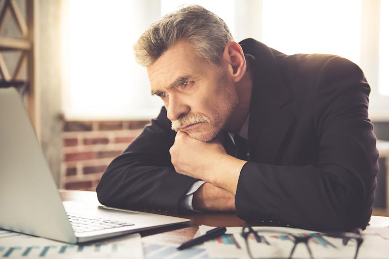 Tired-looking businessman looking at his laptop while propping up his chin with his left hand.