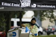 A poll worker drops off a vote-by-mail ballot at a ballot drop box at Miami-Dade County Election Department in Miami, Florida on October 19, 2020