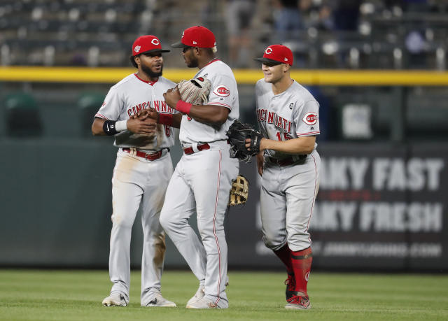 From left, Cincinnati Reds left fielder Phillip Ervin, right fielder Yasiel Puig and center fielder Nick Senzel congratulate each other after the ninth inning of a baseball game against the Colorado Rockies Saturday, July 13, 2019, in Denver. The Reds won 17-9. (AP Photo/David Zalubowski)