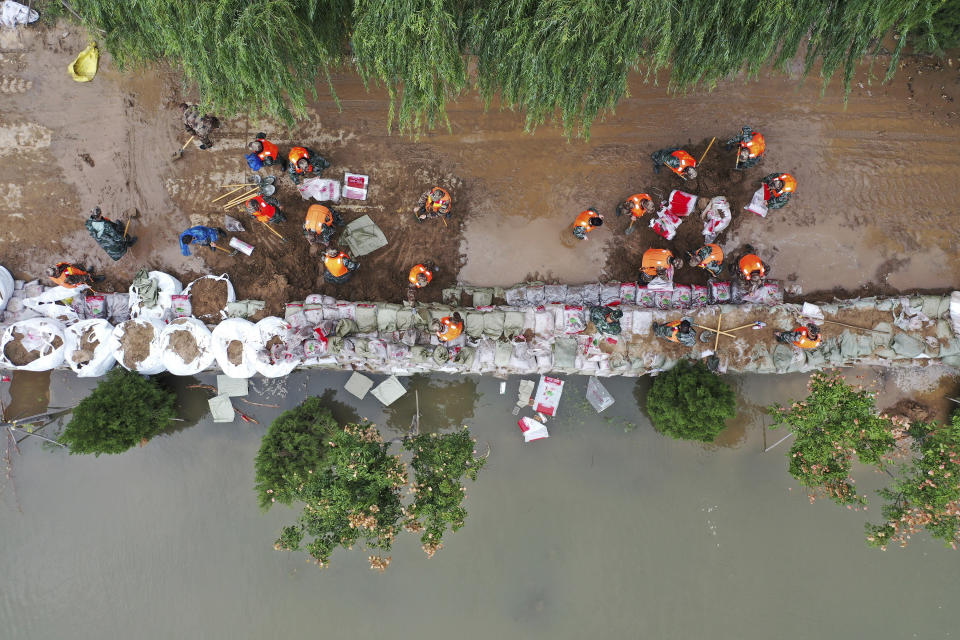 In this photo released by Xinhua News Agency, an aerial photo shows rescuers fortifying a temporary dyke against the flooding at the Lianbo Village in Hejin City, in northern China's Shanxi Province, Sunday, Oct. 10, 2021. (Zhan Yan/Xinhua via AP)