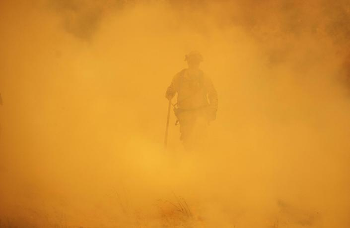 A firefighter walks through smoke during the Mendocino Complex Fire in Lakeport.