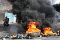Men ride a motorbike past burning tires blocking a street during a protest targeting the government over an economic crisis, in Nabatiyeh