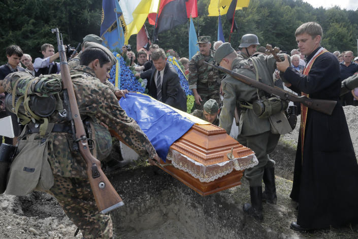 An Orthodox priest prays as Ukrainians dressed in the SS Galician Division uniform carry a coffin with remains of a Division soldier at the SS Galician Division cemetery during re-burial ceremony near the village of Chervone in western Ukraine on Sunday, July 21, 2013. Western Ukraine marked the 70th anniversary of creation of the SS Galician Division. (AP Photo/Efrem Lukatsky)