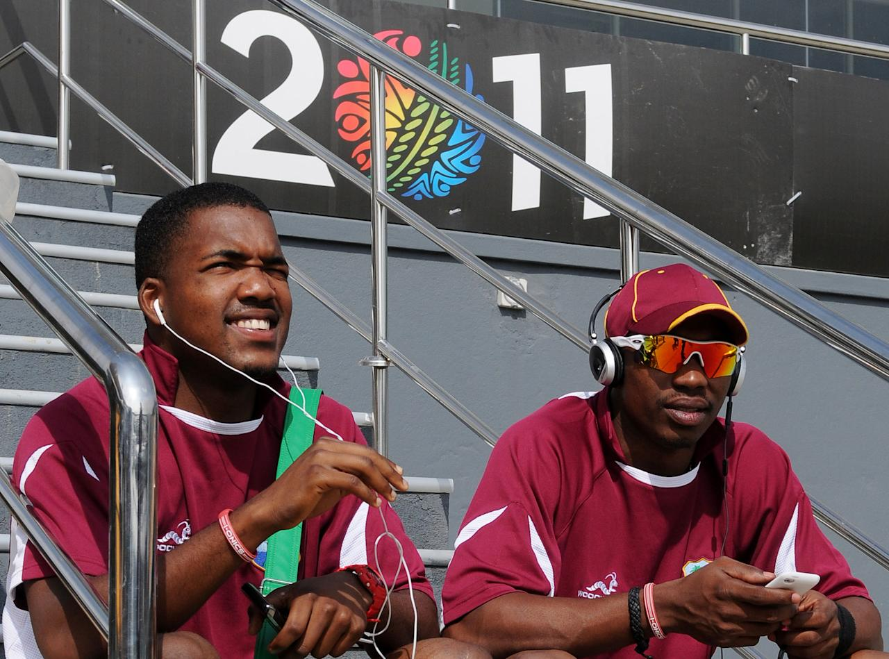 West Indies cricketers Darren Bravo (L) and teammate Dwayne Bravo (R) listen to music as they relax during a practice session at The R.Peremadasa Stadium in Colombo on February 11, 2011. The West Indies first warm-up match in preparation for the 2011 Cricket World Cup is set to take place against Kenya on February 12, 2011. The 2011 Cricket World Cup event takes place in India, Sri Lanka and Bangladesh from February 19-April 2 with 14 nations taking part in the marathon six-week tournament. AFP PHOTO/Lakruwan WANNIARACHCHI
