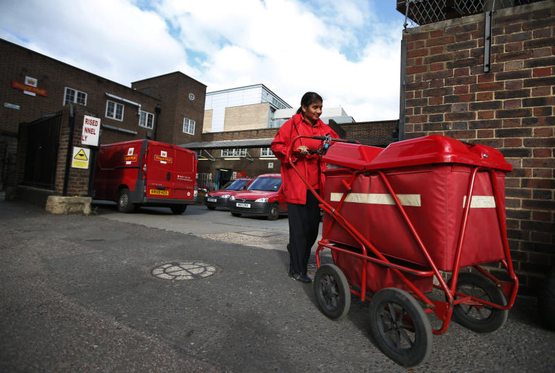 A Royal Mail post officer walks out of a Post Office depot in London, Thursday, Oct. 10, 2013. British Business Secretary Vince Cable defended the government's sale of a majority stake in Royal Mail on Wednesday, saying that more than 700,000 retail investors have sought shares in the initial public offering. Shares are expected to be priced at between 260 pence and 330 pence, giving Royal Mail a market valuation of between 2.6 billion pounds (4.1 billion US dollars) and 3.3 billion pounds. The government would raise between 1.04 billion pounds and 1.72 billion pounds based on these figures.(AP Photo/Lefteris Pitarakis)