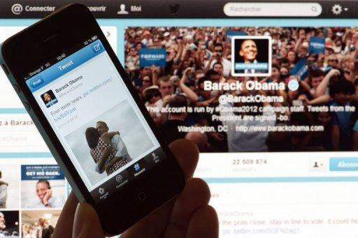 A person poses with a cell phone in front of a computer screen to check Barack Obama's tweet after his re-election as US president. Obama sealed his tech-savvy reputation late Tuesday by announcing his victory over Republican foe Mitt Romney on Twitter and Facebook with the photo