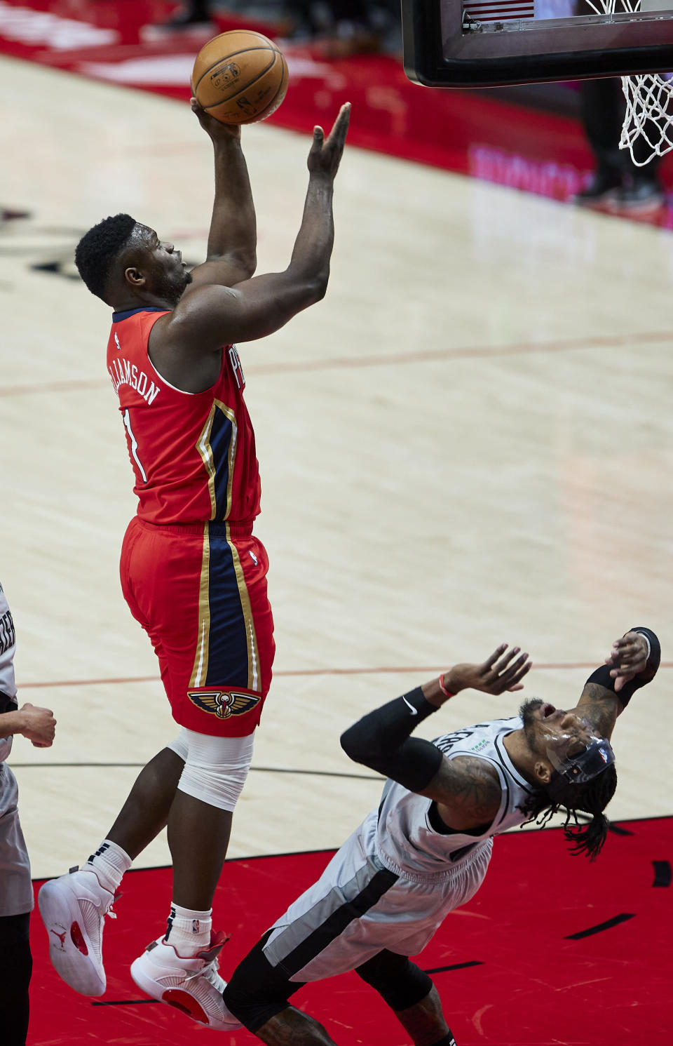 New Orleans Pelicans forward Zion Williamson, left, shoots over Portland Trail Blazers forward Robert Covington during the first half of an NBA basketball game in Portland, Ore., Tuesday, March 16, 2021. (AP Photo/Craig Mitchelldyer)