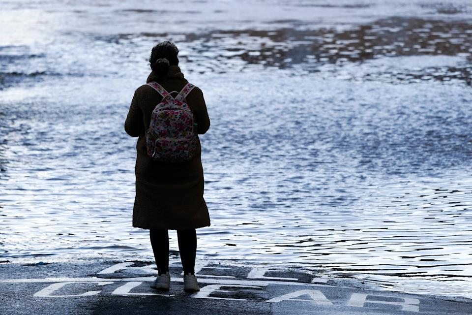 A woman looks out over the River Ouse in York as it floods following rain and melting snow on January 21, 2021 in York, England. (Getty Images)