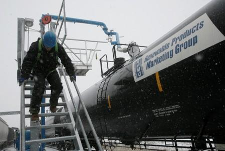 FILE PHOTO: Slade Whetro slides down a stairway alongside a railroad tank car loaded with ethanol at the Lincolnway Energy plant in Nevada, Iowa