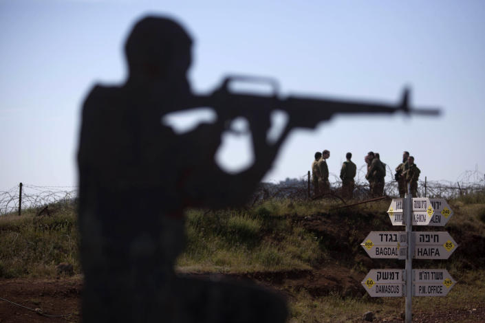 In this photo taken Wednesday, April 24, 2013, Israeli soldiers stand next to a metal placard in the shape of an Israeli soldier, at an observation point on Mt. Bental in the Golan Heights, Against a breathtaking vista of green fields and a snowcapped mountain range, all is silent but for a strong gust of wind whipping across the landscape. The tranquility is suddenly interrupted by a burst of gunfire from beyond a newly built fortified fence: Jihadi rebels are battling with Bashar Assad's battered troops in a nearby Syrian village. Watching it all unfold are Israeli soldiers atop tanks - a sight unseen here in a generation - and the sounds of explosions from a large-scale Israeli drill are distinctly heard in the background. (AP Photo/Sebastian Scheiner)