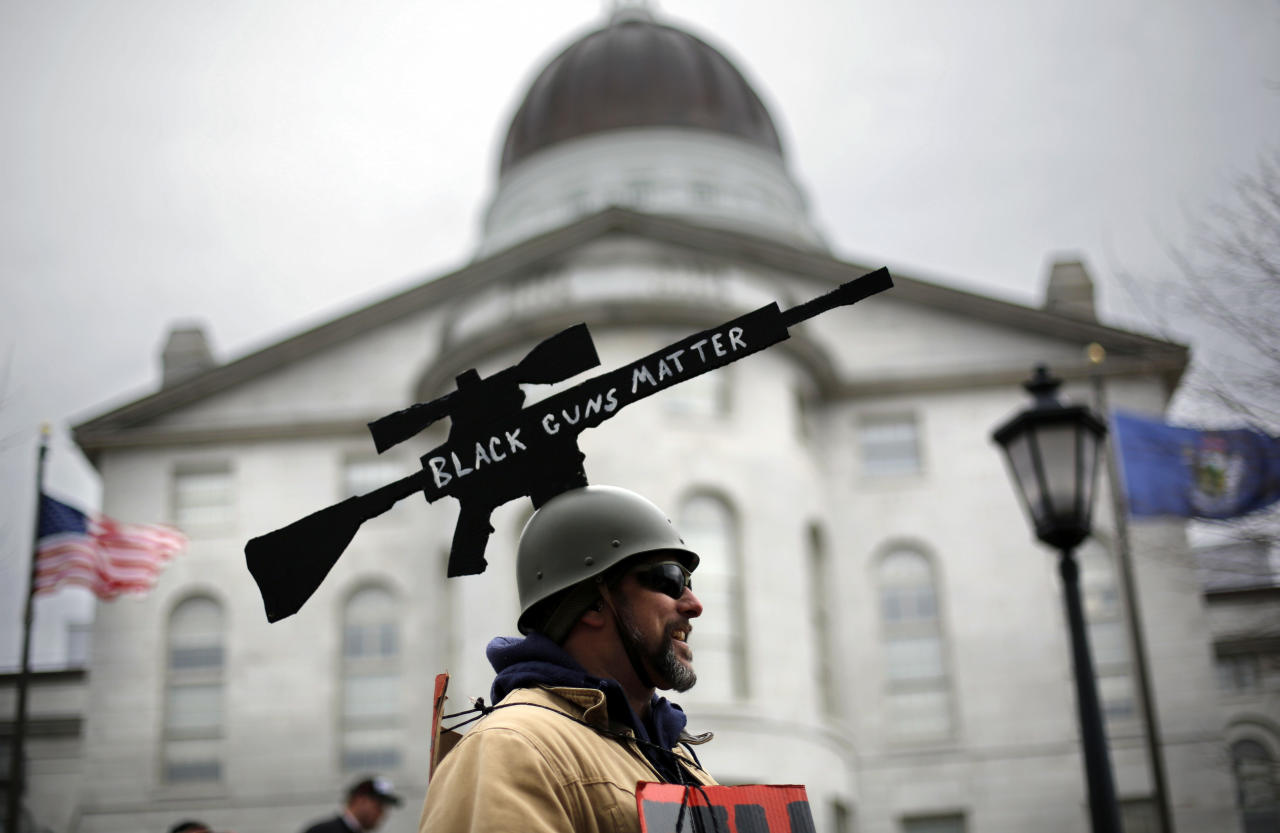 <p>Joe Dobbins of Hartford, Maine, wears a cut-out of an AR-10 tactical rifle while attending a gun rights rally, Saturday, April 14, 2018, at the State House in Augusta, Maine. (Photo: Robert F. Bukaty/AP) </p>