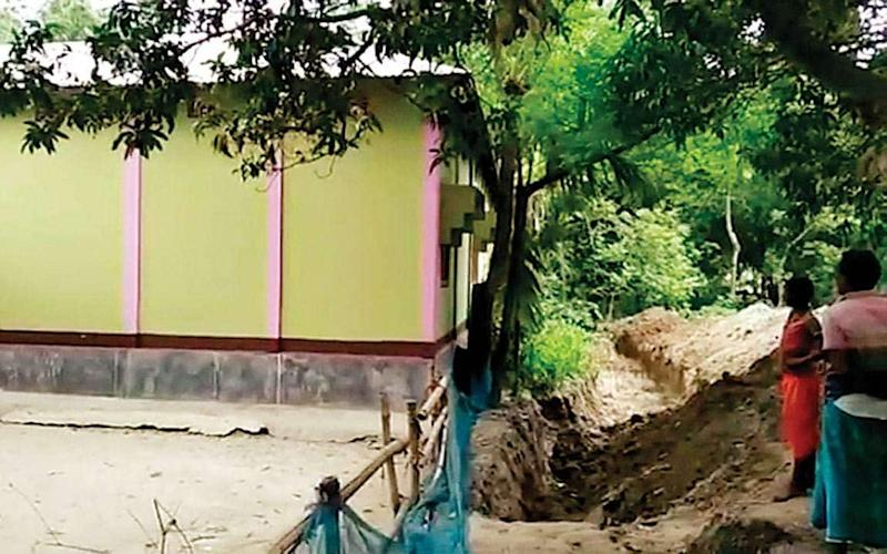 Villagers dig trench around the man's house