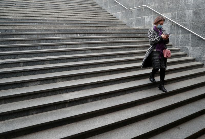 A woman wearing a protective face mask uses her smartphone as she walks in an underpass in Kyiv
