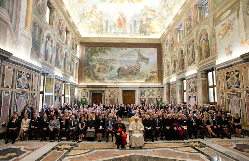 In this photo provided by the Vatican newspaper L'Osservatore Romano, Pope Francis, in white at front, poses with the Patrons of the Arts of the Vatican Museum, a fundraising organization for restoring the Vatican's artistic treasures, on the occasion of their audience, at the Clementine Hall, at the Vatican, Saturday, Oct. 19, 2013. The donors to the Vatican Museums got serious VIP treatment during their recent visit to Rome: lectures on museum restoration projects, individual chats with Pope Francis, catered dinners in museum galleries and a blockbuster vespers service in the Sistine Chapel celebrated by Monsignor Georg Gaenswein, the man who has the ear of two popes. Such access comes with a price, but it's not nearly as high as you might think. In one of the greatest bargains at the Vatican, all it takes is 500 US dollars a year to join the Patrons. (AP Photo/L'Osservatore Romano, ho)