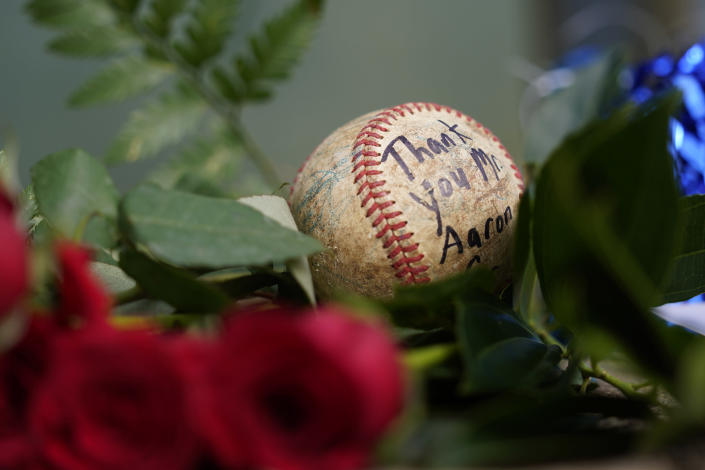 A baseball left by a fan rests in a growing memorial Friday, Jan. 22, 2021, in Atlanta, near the spot where a ball hit for home run by Atlanta Braves' Hank Aaron cleared the wall to break Babe Ruth's home run record in 1974. Aaron, who endured racist threats with stoic dignity during his pursuit of Babe Ruth but went on to break the career home run record in the pre-steroids era, died peacefully in his sleep early Friday. He was 86. (AP Photo/John Bazemore)