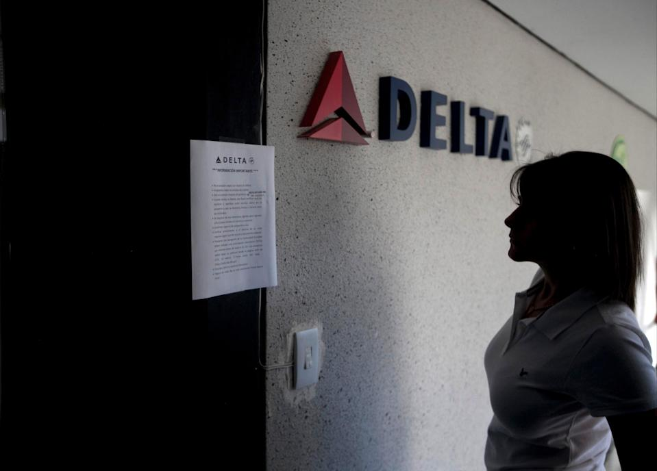 A woman reads a notice on the door of a closed Delta Airlines office in Caracas, Venezuela, Friday, Jan. 24, 2014. American Airlines, United and Panama's Copa Airlines were also among carriers whose offices were either closed or had halted sales on Friday after the government devalued the local currency, the Bolivar, for flights abroad. (AP Photo/Alejandro Cegarra)