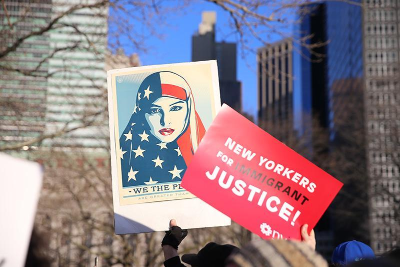 <p>People hold up signs as they gather for a rally in New York's Battery Park in New York, Jan. 29, 2017, protesting President Donald Trump's immigration order. (Photo: Gordon Donovan/Yahoo News) </p>