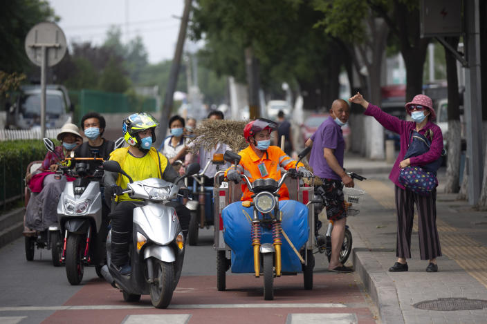 People wearing face masks to protect against the new coronavirus wait at an intersection near the Xinfadi wholesale food market district in Beijing, Saturday, June 13, 2020. Beijing closed the city's largest wholesale food market Saturday after the discovery of seven cases of the new coronavirus in the previous two days. (AP Photo/Mark Schiefelbein)