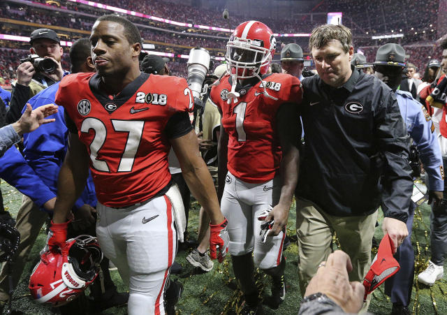 Georgia's Nick Chubb, from left, Sony Michel and Kirby Smart walk off the field as Georgia loses to Alabama in the NCAA college football playoff championship game in Atlanta on Monday, Jan. 8, 2018. Alabama won, 26-23. (Curtis Compton/Atlanta Journal-Constitution via AP)