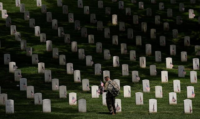 <p>A soldier from the 3rd U.S. Infantry Regiment (Old Guard) takes part in Flags-in, where a flag is placed at each of the 284,000 headstones at Arlington National Cemetery ahead of Memorial Day, in Arlington, Va., May 25, 2017. (Kevin Lamarque/Reuters) </p>
