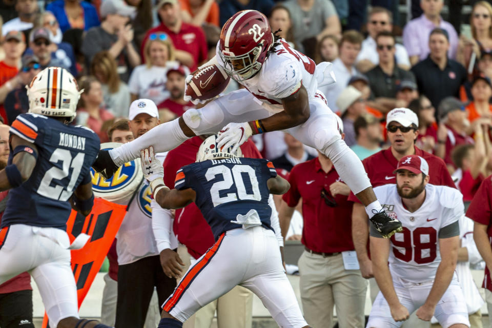 Alabama running back Najee Harris (22) hurdles Auburn defensive back Jeremiah Dinson (20) during the first half of an NCAA college football game, Saturday, Nov. 30, 2019, in Auburn, Ala. (AP Photo/Vasha Hunt)