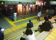 Passengers wait sitting on stairs as the train services are suspended due to an earthquake at JR Shinagawa station in Tokyo, Thursday, Oct. 7, 2021. A powerful earthquake shook the Tokyo area on Thursday night, but officials said there was no danger of a tsunami.(Kyodo News via AP)