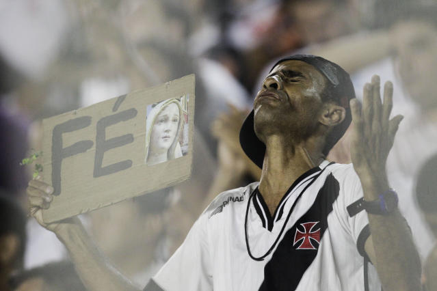 "FILE - In this Nov. 9, 2011 file photo, a fan of Brazil's Vasco da Gama soccer club reacts holding a sign that reads in Portuguese: ""Faith"", at the end of a Copa Sudamericana quarterfinal soccer match against Peru's Universitario in Rio de Janeiro, Brazil. Brazilians fans idolize their stars on the fields, courts and tracks. They'll cheer loudly at any sporting event they'll go to, be it a World Cup match, a Formula One race or a mixed martial arts fight. (AP Photo/Felipe Dana, File)"