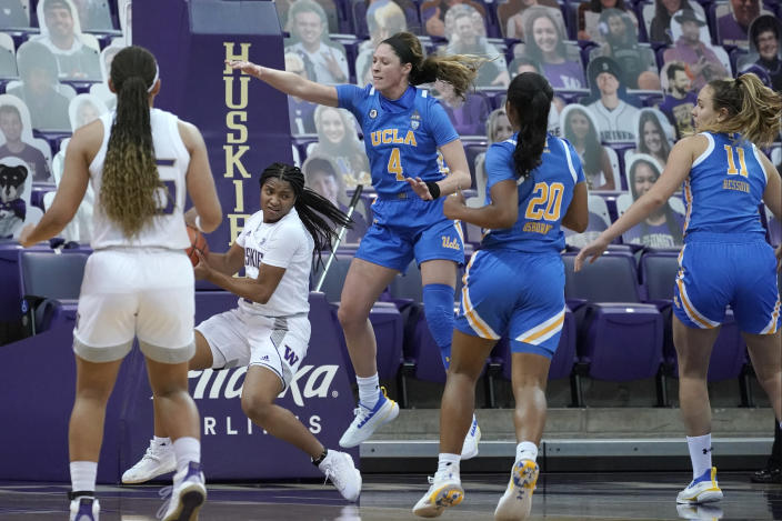 UCLA guard Lindsey Corsaro (4) and guard Charisma Osborne (20) watch as Washington guard Tameiya Sadler, second from left, looks to pass during the second half of an NCAA college basketball game, Sunday, Feb. 7, 2021, in Seattle. (AP Photo/Ted S. Warren)