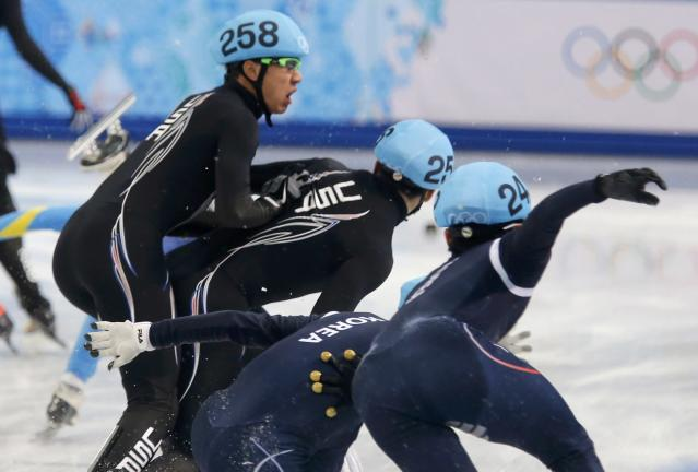 U.S. skaters and South Korea's skaters crash during the men's 5,000 metres short track speed skating relay semi-final event at the Iceberg Skating Palace during the 2014 Sochi Winter Olympics February 13, 2014. REUTERS/Alexander Demianchuk (RUSSIA - Tags: SPORT SPEED SKATING OLYMPICS)