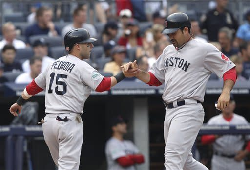 Boston Red Sox's Dustin Pedroia, left, and Adrian Gonzalez celebrate after scoring on a double by Will Middlebrooks during the first inning of the baseball game against the New York Yankees at Yankee Stadium in New York, Saturday, July 28, 2012. (AP Photo/Seth Wenig)