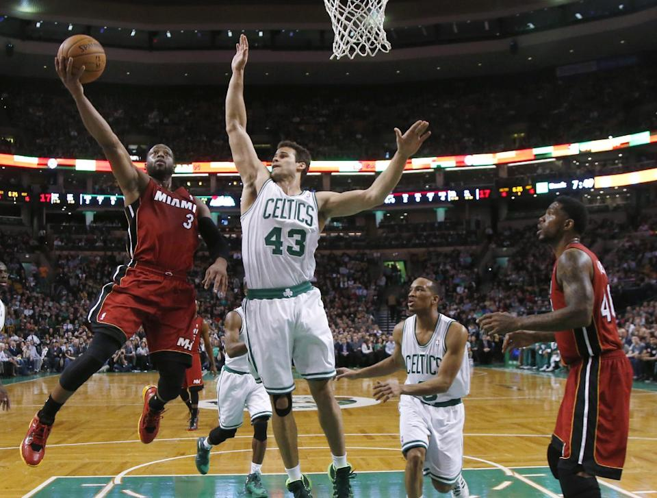 Miami Heat guard Dwyane Wade (3) drives to the basket against Boston Celtics center Kris Humphries (43) as Celtics guard Avery Bradley (0) and Heat forward Udonis Haslem (40) watch in the first quarter of an NBA basketball game in Boston Wednesday, March 19, 2014. (AP Photo/Elise Amendola)