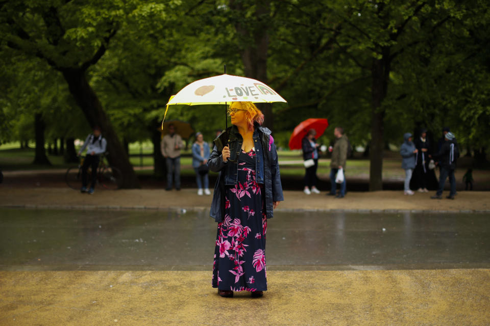 A woman holds an umbrella prior to a protest against COVID-19 restriction measures at the Bois de la Cambre park in Brussels, Saturday, May 15, 2021. (AP Photo/Francisco Seco)