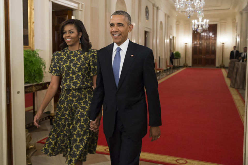<p>The First couple arrived hand-in-hand to recognize 17 people with the nation's highest civilian award, the Presidential Medal of Freedom, in the East Room of the White House in Washington, DC. Barbara Streisand, Steven Spielberg, Yogi Berra, NASA mathematician Katherine G. Johnson, and more were among the honorees. While the president wore a black suit with a blue tie, his wife went for something less classic in a chartreuse and forest green print dress from Michael Kors. <i>Photo: AP</i></p>