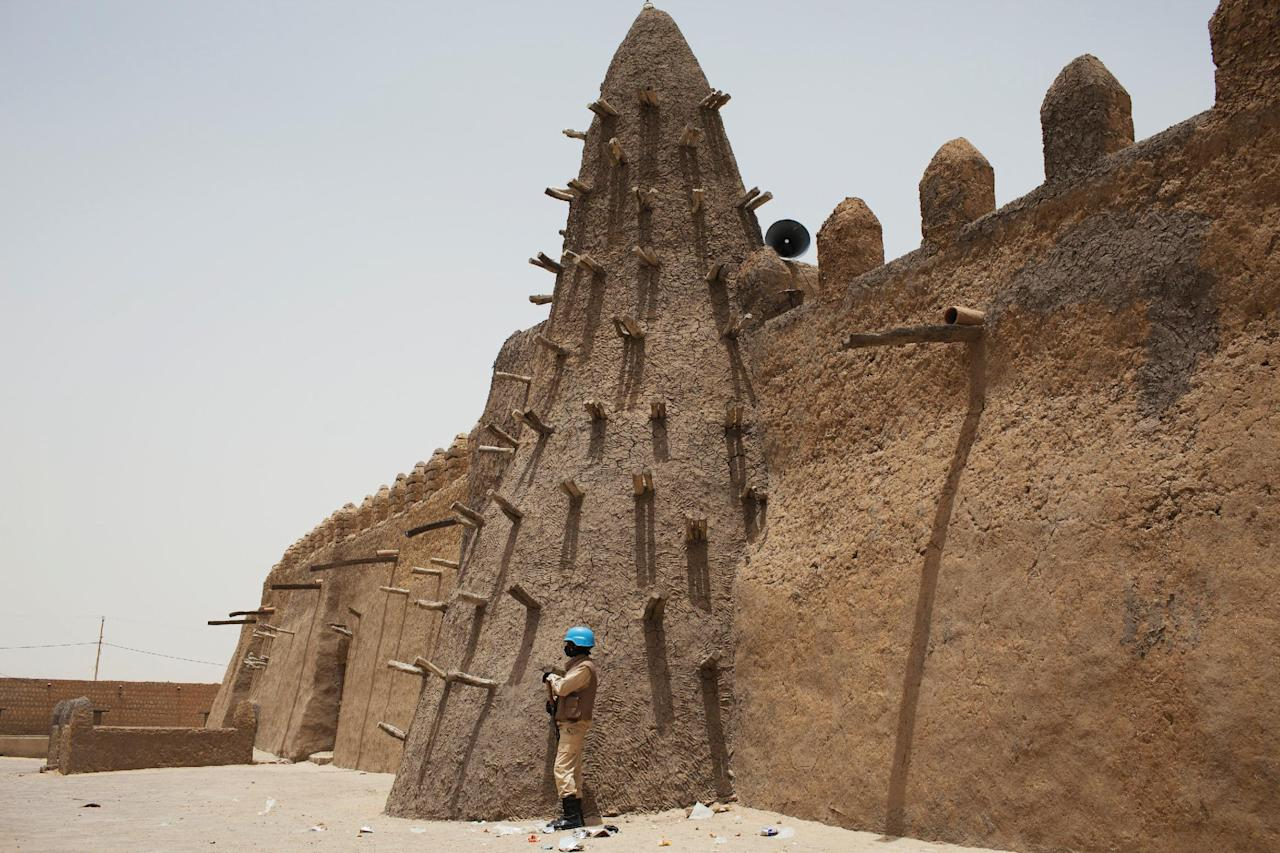 A UN peacekeeper from Burkina Faso stands guard at the Djinguereber mosque, built in the 14th century, during a visit by a UN delegation on election day in Timbuktu, Mali, July 28, 2013.  REUTERS/Joe Penney/Files     TPX IMAGES OF THE DAY