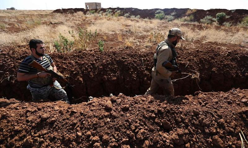 Syrian rebel fighters walk in a newly dug trench in the village of al-Zakat in the northern countryside of Hama province on 17 September.