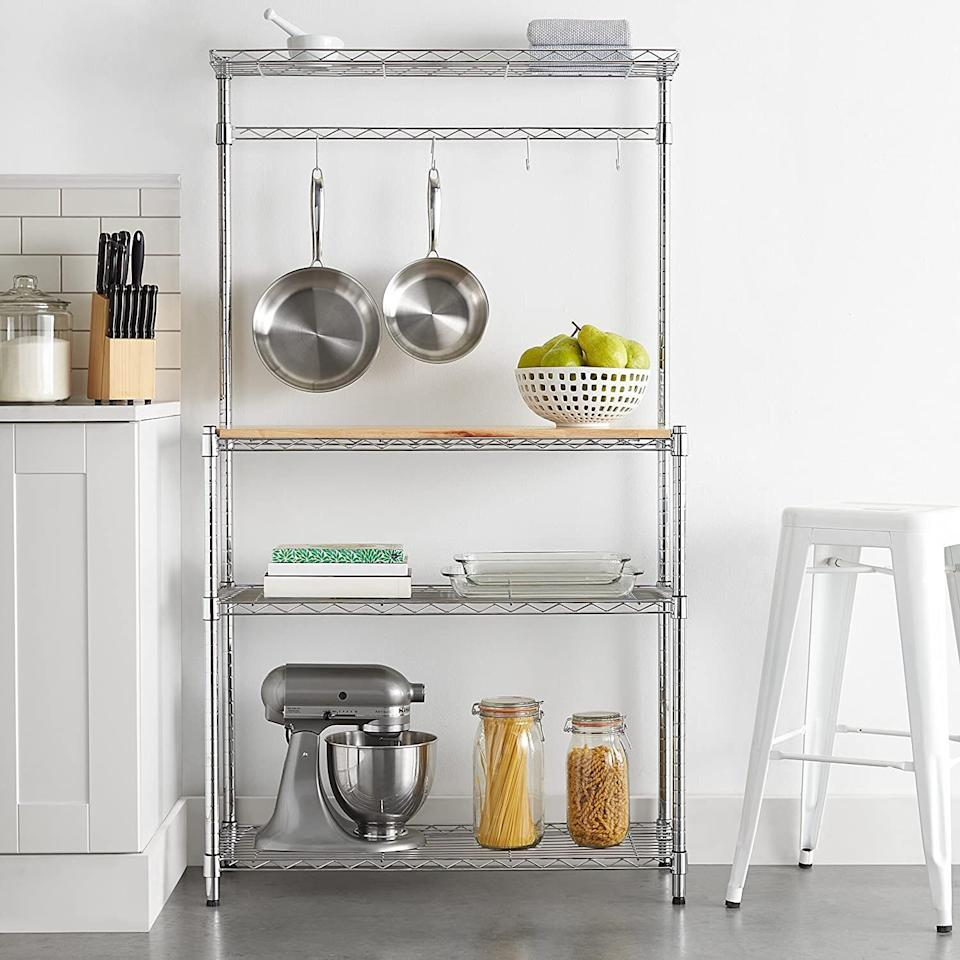 """Organize the clutter on your countertop and make your kitchen more usable. This has plenty of storage space for all the small appliances you love but don't use that often (looking at you, pasta maker!), as well as hooks for hanging pots and pans. You can even use the wood top as extra prep space!<br /><br /><strong>Promising review:</strong>""""Fits perfectly in corner of my kitchen.<strong>Holds all my small and not-so-small appliances that were cluttering my counter space.</strong>I like the top shelf and the hooks. I'm using the hooks for potholders and the top shelf for a few seasonal knickknacks that I'll switch out. I purchased additional hooks that I hang on the side and use for my keys. I also bought some <a href=""""https://amzn.to/3vQ3GYi"""" target=""""_blank"""" rel=""""noopener noreferrer"""">shelf liner</a>, which makes it easy to remove and replace the appliances without them getting snagged on the open shelves.<strong>It went together fairly easy. It's heavy and sturdy. Lots of space on this basic kitchen organizer and I consider it an excellent purchase!</strong>"""" --<a href=""""https://amzn.to/3us1mXs"""" target=""""_blank"""" rel=""""noopener noreferrer"""">JoLi</a><br /><br /><strong>Get it from Amazon for <a href=""""https://amzn.to/3h73iAT"""" target=""""_blank"""" rel=""""noopener noreferrer"""">$89.44</a>.</strong>"""