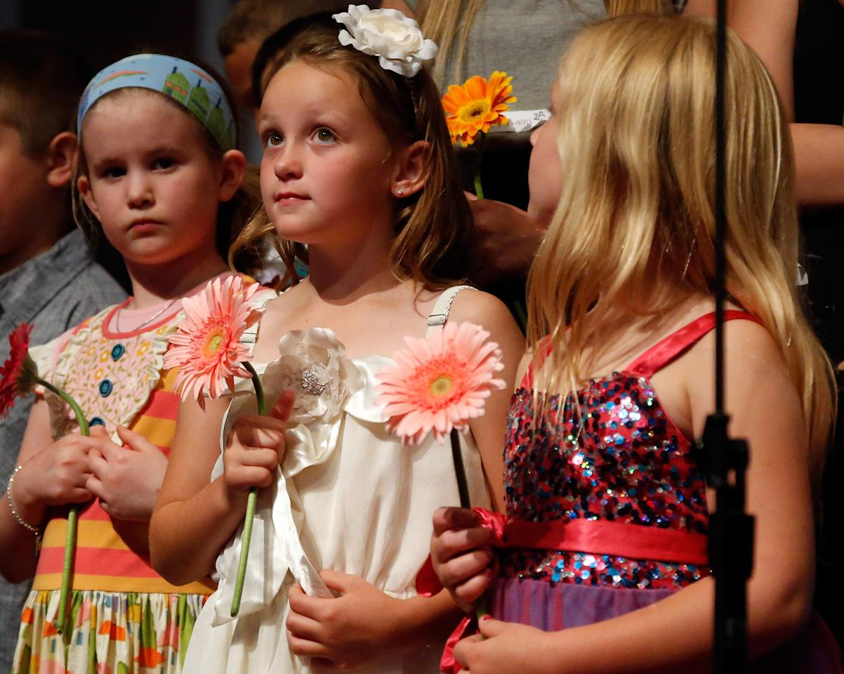 MOORE, OK - MAY 26:  (L-R) Students Mary Kate Pauley, Madison Perkins, and Isabel White stand on stage during the Oklahoma Strong memorial service held to honor victims of the recent deadly tornado at the First Baptist Church on May 26, 2013 in Moore, Oklahoma. The tornado of EF5 strength and two miles wide touched down May 20 killing at least 24 people and leaving behind extensive damage to homes and businesses. U.S. President Barack Obama visited the area Sunday and promised federal aid to supplement state and local recovery efforts.  (Photo by Sue Ogrocki-Pool/Getty Images)