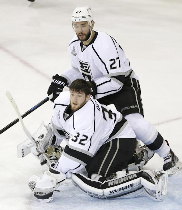 Los Angeles Kings goalie Jonathan Quick (32) loses his mask as defenseman Alec Martinez (27) helps defend against the New York Rangers in the third period during Game 3 of the NHL hockey Stanley Cup Final, Monday, June 9, 2014, in New York. The Kings won 3-0. (AP Photo/Frank Franklin II)