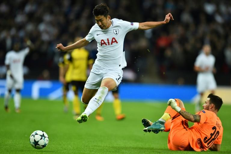 Tottenham Hotspur's striker Son Heung-Min (L) takes the ball past Borussia Dortmund's goalkeeper Roman Buerki (R) during the UEFA Champions League on September 13, 2017