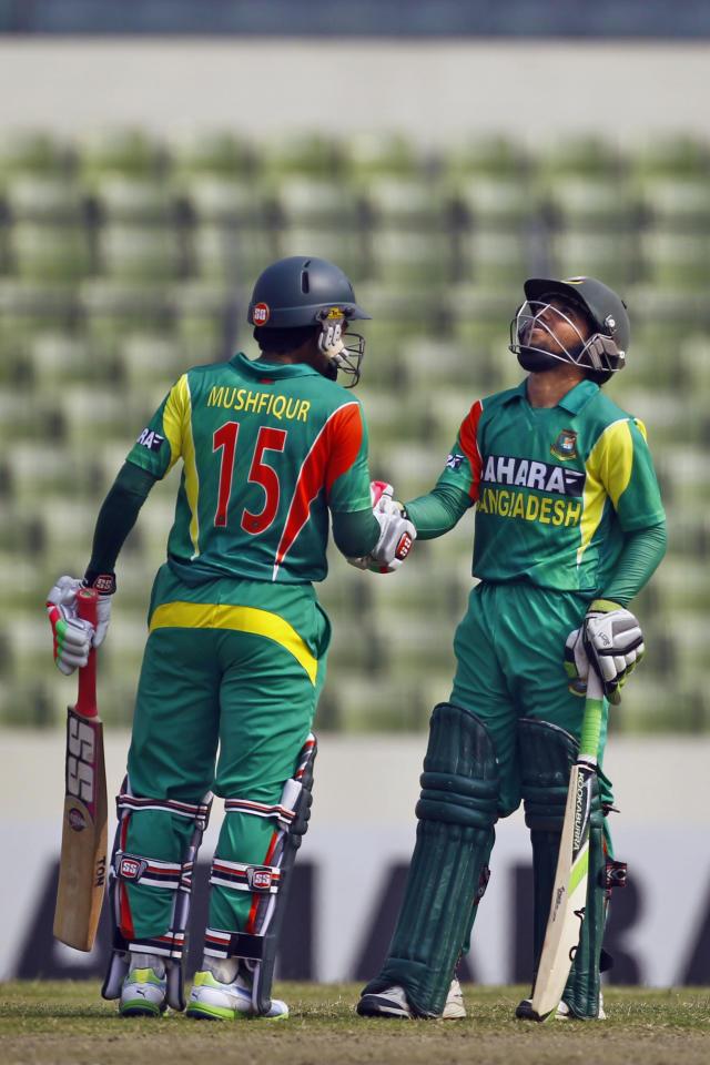 Bangladesh's Mominul Haque, right, is congratulated by teammate Mushfiqur Rahim for scoring fifty runs on the third one day international cricket against Sri Lanka in Dhaka, Bangladesh, Saturday, Feb. 22, 2014. (AP Photo/A.M. Ahad)