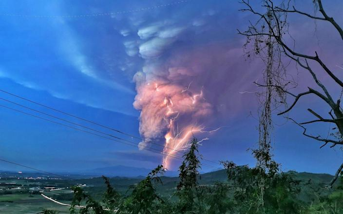 Lightning streak over Batangas as Taal Volcano continues its eruption on Sunday evening. - https://www.alamy.com