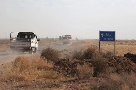 Vehicles drive on a road north of Raqqa city