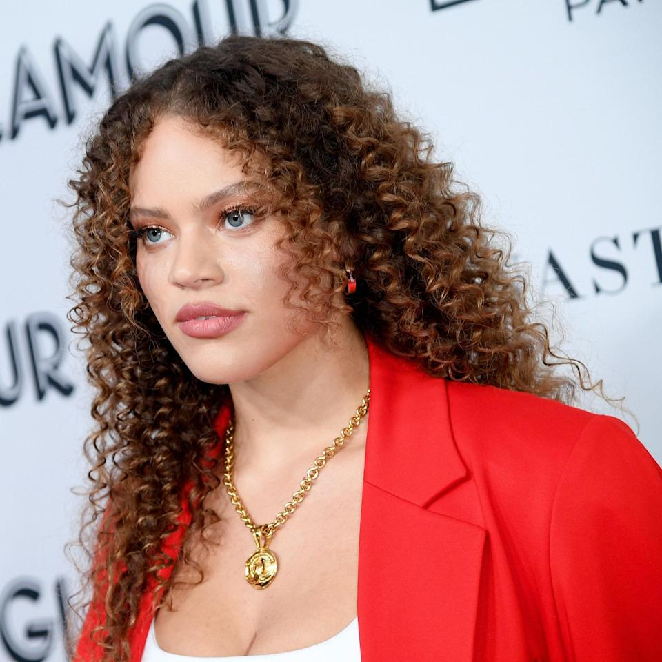 """Look closely and you'll see that model Solange van Doorn has long bangs framing her face. These collapsed layers help reduce the weight of her overall hair (which may be beneficial as the heavier the hair, the more it can expand and become very round or triangular based on the curl pattern). Shorter says to use a <a href=""""https://www.allure.com/gallery/best-curl-creams-under-20?mbid=synd_yahoo_rss"""" rel=""""nofollow noopener"""" target=""""_blank"""" data-ylk=""""slk:curl enhancer"""" class=""""link rapid-noclick-resp"""">curl enhancer</a> for cuts that build volume. Then, twirl your hair in large sections around your finger, she instructs. Finish by diffusing and scrunching your hair with a blow-dryer like the <a href=""""https://shop-links.co/1740956912948655026"""" rel=""""nofollow noopener"""" target=""""_blank"""" data-ylk=""""slk:Bio Ionic Power Diva Pro Styler Dryer"""" class=""""link rapid-noclick-resp"""">Bio Ionic Power Diva Pro Styler Dryer</a>."""