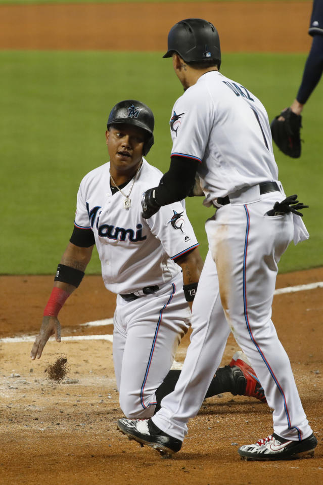 Miami Marlins' Isan Diaz (1) and Starlin Castro, left, congratulate each other after they scored on a double by Harold Ramirez during the first inning of a baseball game against the Atlanta Braves, Sunday, Aug. 11, 2019, in Miami. (AP Photo/Wilfredo Lee)