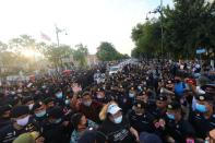 Police scuffle with a group of anti-government demonstrators near the royal motorcade carrying Thailand's Queen Suthida and Prince Dipangkorn in front of the Government House in Bangkok