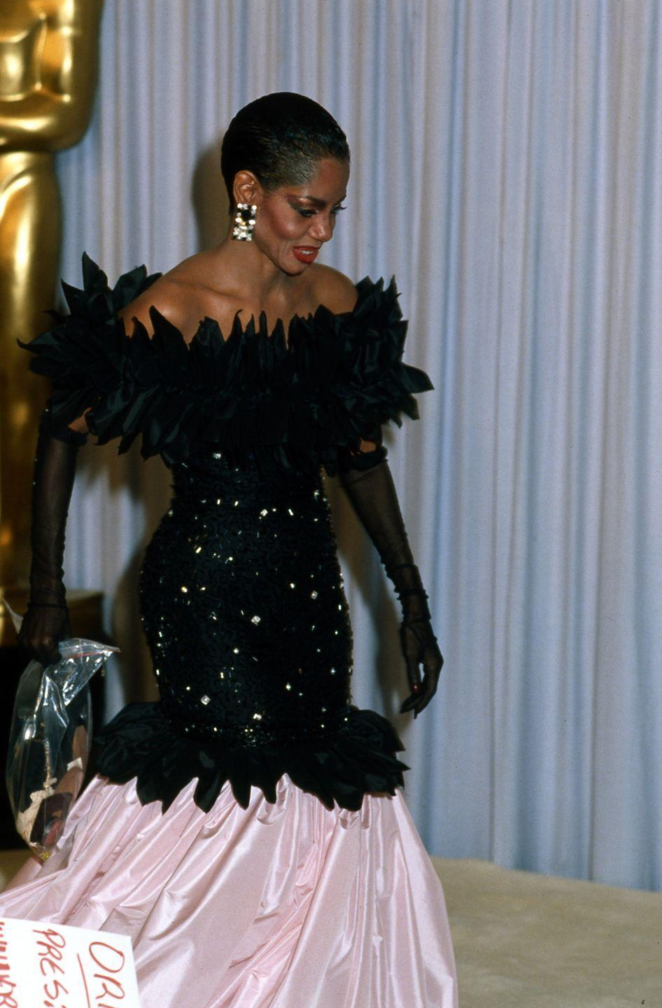 "<p>The singer stunned in this two-toned gown complete with a feathered top and sheer gloves. She performed the ever-so-romantic ballad Take My Breath Away"" with Lou Rawls at the ceremony. </p>"