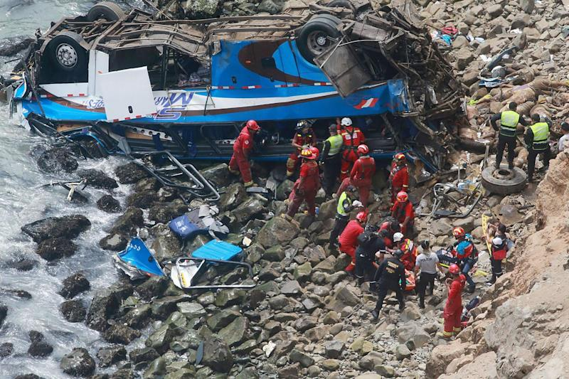 Emergency workers at the scene of the bus crash in Pasamayo, Peru: EPA