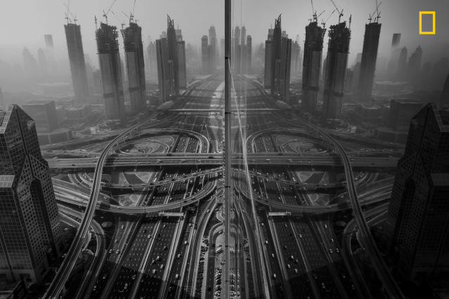 "<p>Photograph and caption by Gaanesh Prasad/National Geographic Travel Photographer of the Year Contest. — ""On an early morning, I wanted to photograph the fog, which is epic in Dubai every year from December to January — and almost every photographer's dream in this part of the world. Sadly, I could not get access to the rooftop and so I peeped through the glazed window on a lower floor. I was overwhelmed and excited to see how beautiful the city looks, and my excitement was quadrupled as soon as I saw the reflection of the road and building on the building that I was in. I immediately opened the window to the maximum permissible amount and clicked a single shot with stretched hands."" Dubai, UAE. </p>"